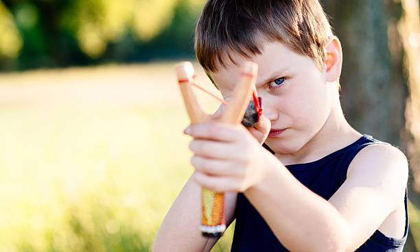 little boy playing with slingshot - mischief stock photos and pictures