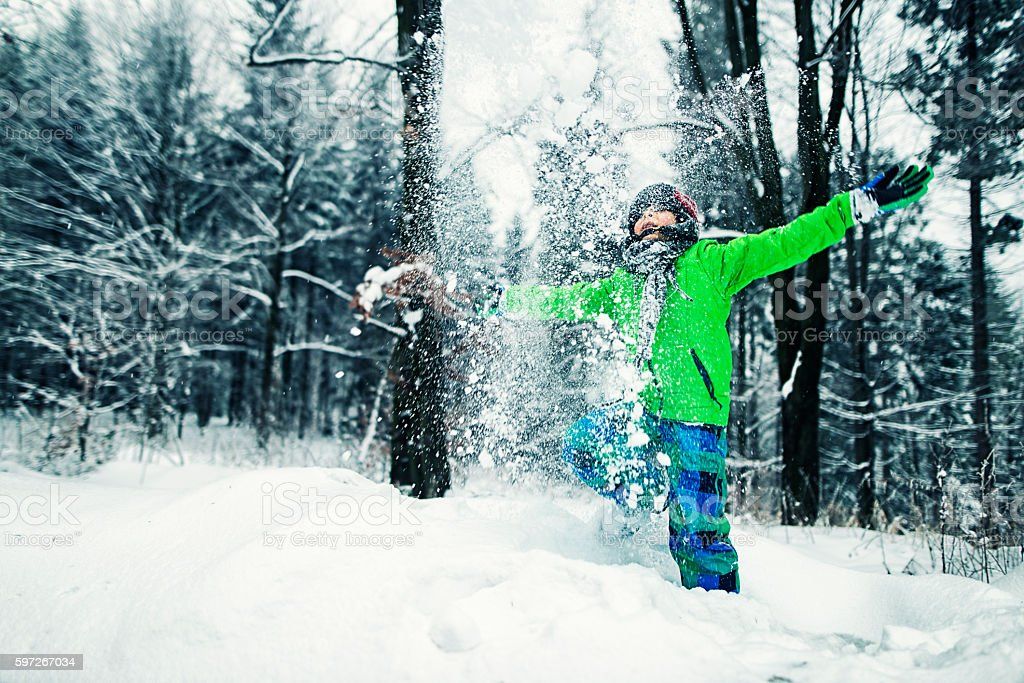 Little boy playing with snow in winter forest royalty-free stock photo
