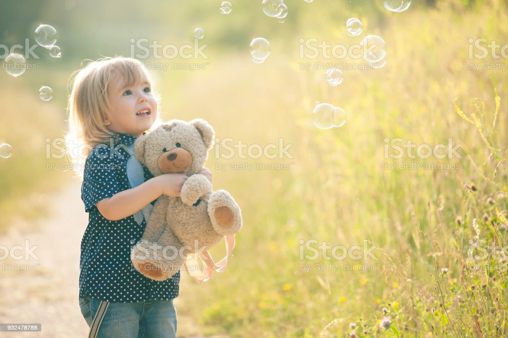 Little boy playing with soap bubbles and bear toy stock photo