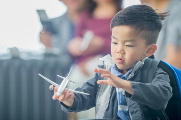 kleiner junge spielt mit spielzeugflugzeug am flughafen - kleinkind busy bags stock-fotos und bilder