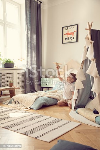 1205865899 istock photo Little boy playing with toy airplane in scandinavian kid playroom with tent 1073649528
