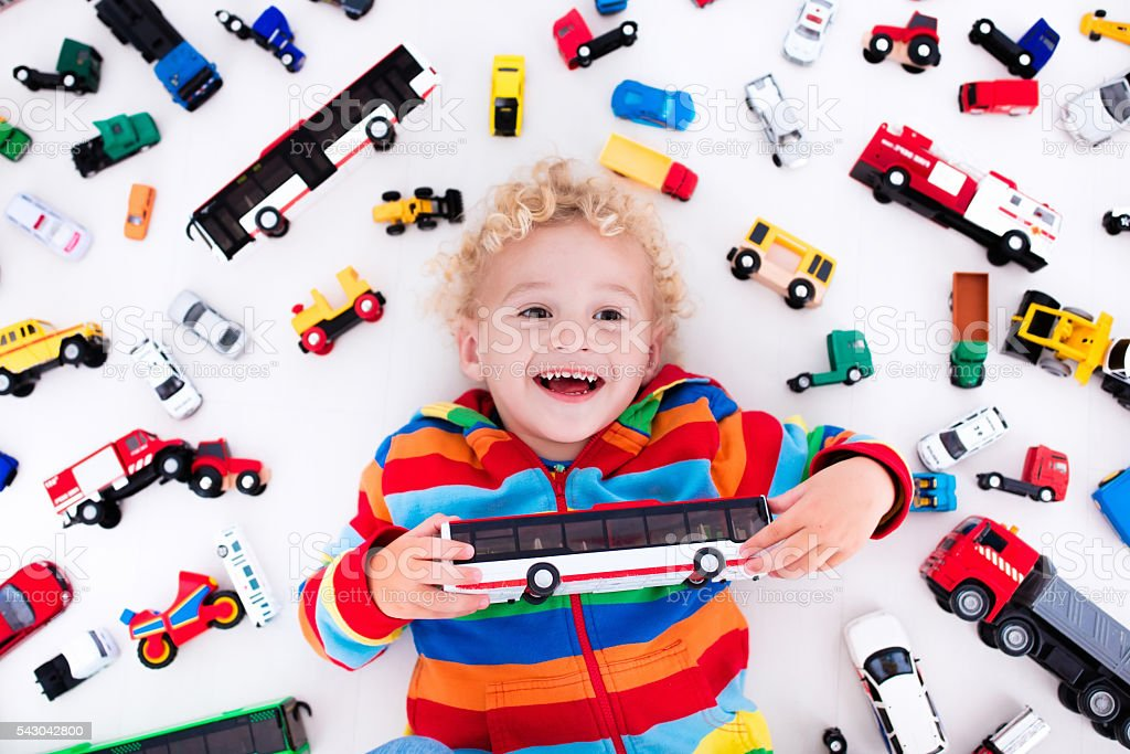 038715ae5 Little boy playing with toy cars holding bus in hands - Stock image .