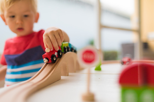 Little boy playing with wooden toy train.