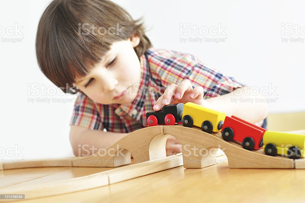 Little boy playing with wooden train stock photo