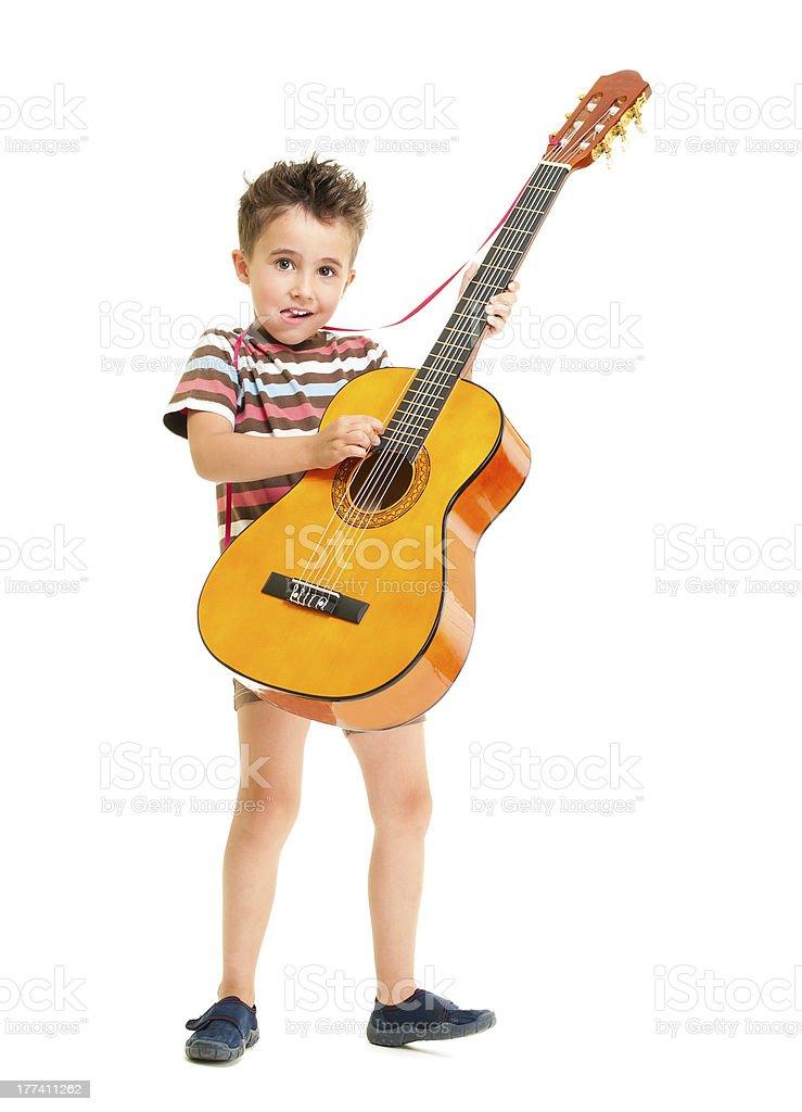 Little boy plays acoustic guitar stock photo
