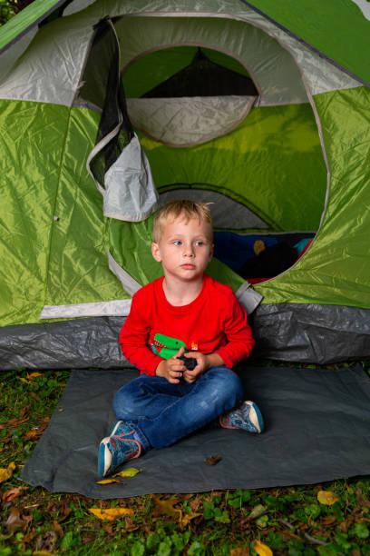 1 Kleiner Junge spielt allein in seinem Hinterhof in einem grünen Campingzelt – Foto