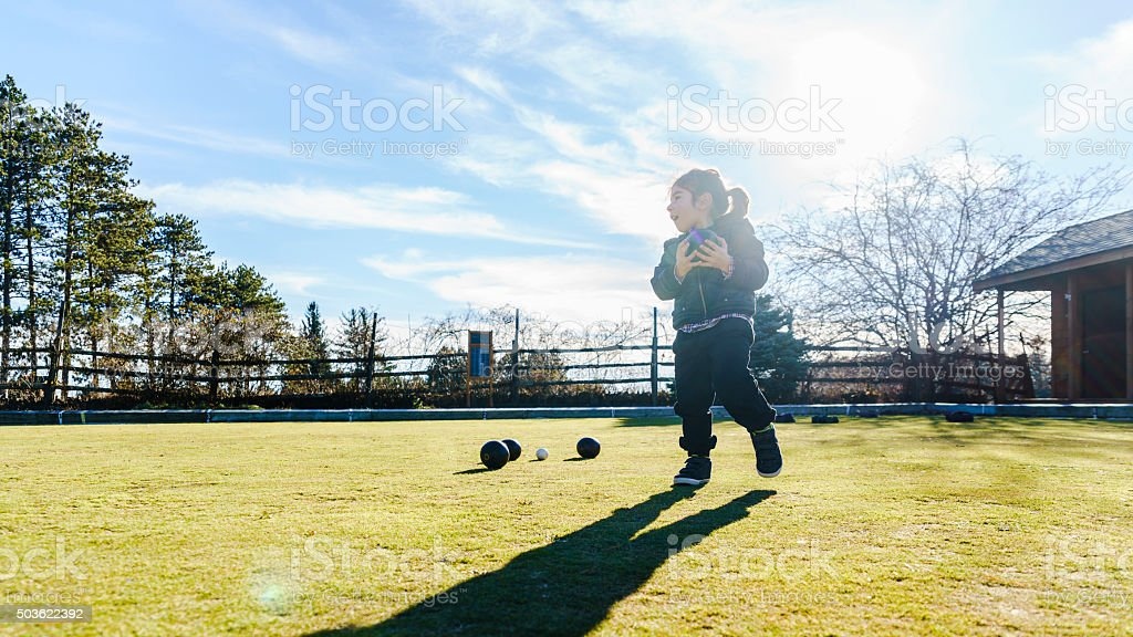 Little boy plays bowls at the lawn stock photo
