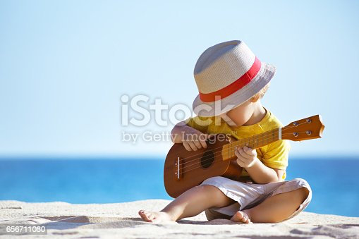 istock Little boy plays guitar ukulele at sea beach 656711080