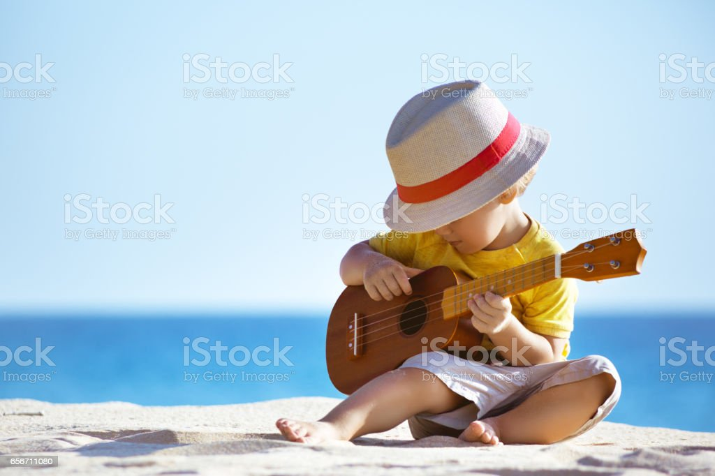 Little boy plays guitar ukulele at sea beach - fotografia de stock