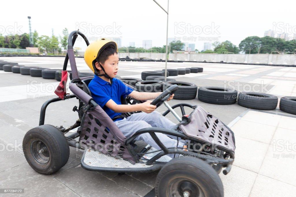 little boy plays in kart circuit stock photo