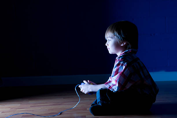 Little boy plays video game in the dark stock photo