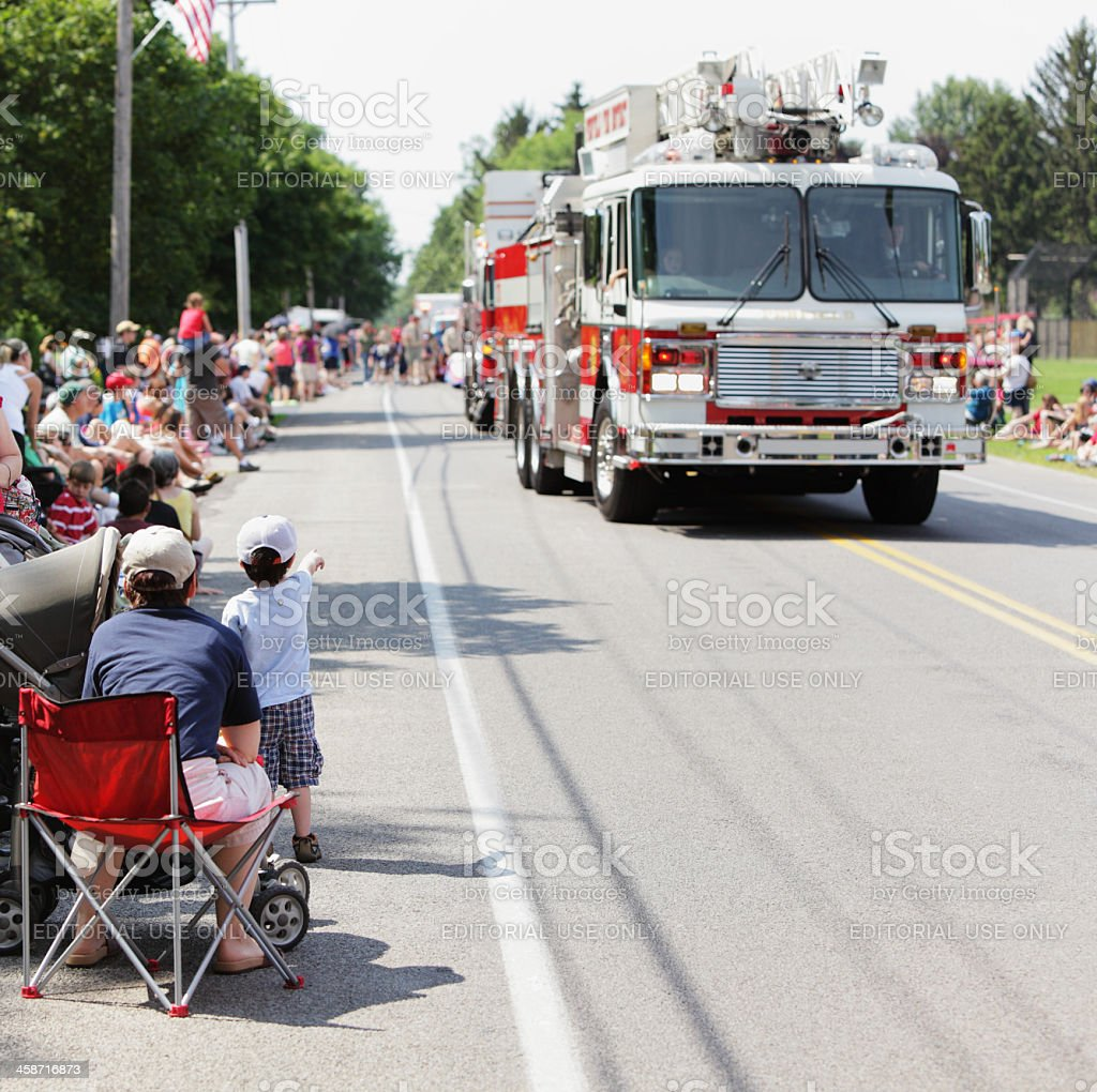 Little Boy Pointing at Fire Engines During Parade stock photo