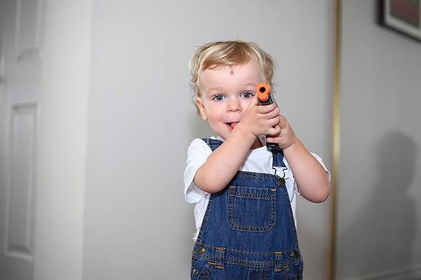 Little boy pointing with his toy-gun Little boy playing with his gun toy at home and looking at camera. Cute Caucasian little boy pointing with a toy gun. Toy-gun and little boy. Child proofing. Danger of fire arms at home. bib overalls boy stock pictures, royalty-free photos & images