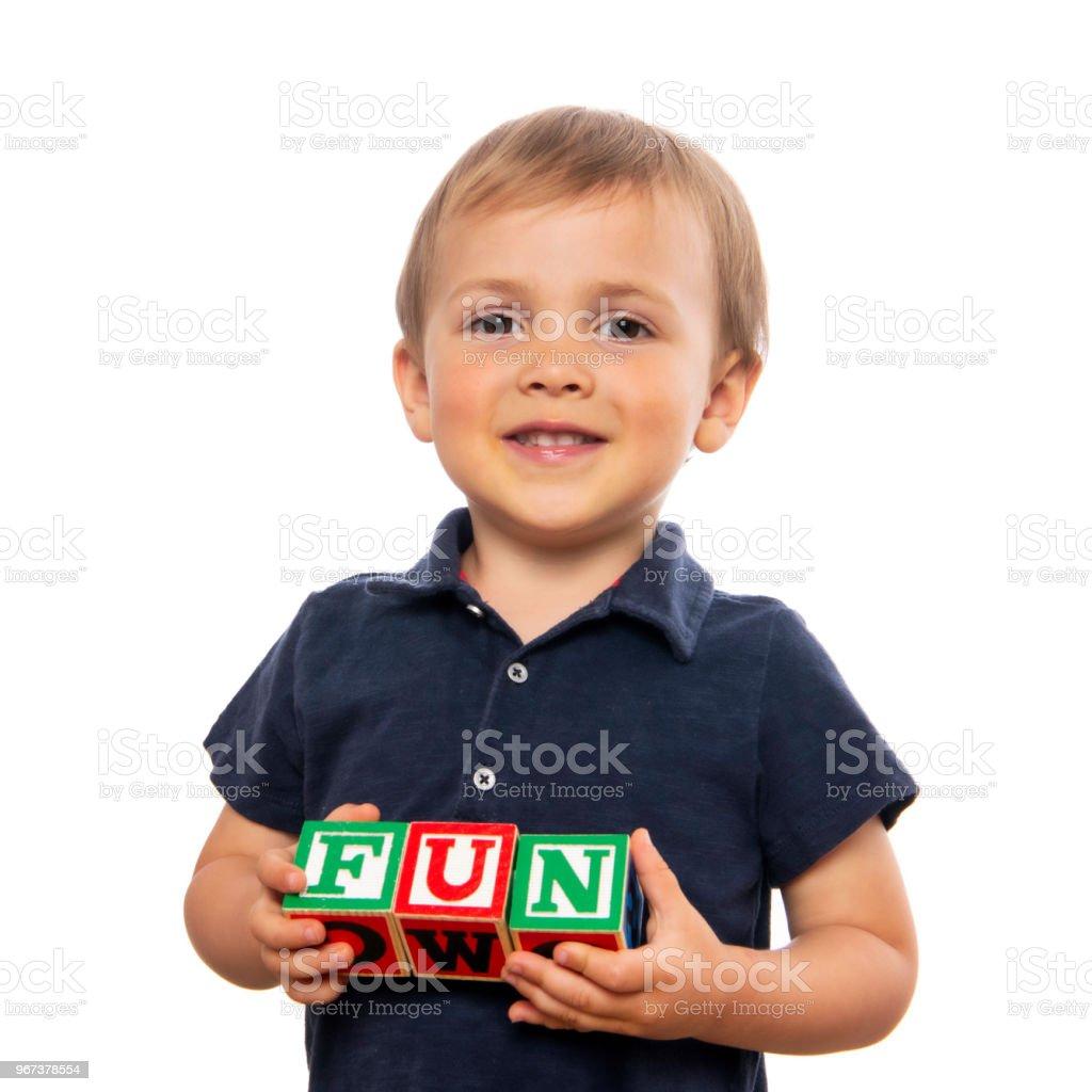 Little boy posing with alphabet blocks on white background stock photo