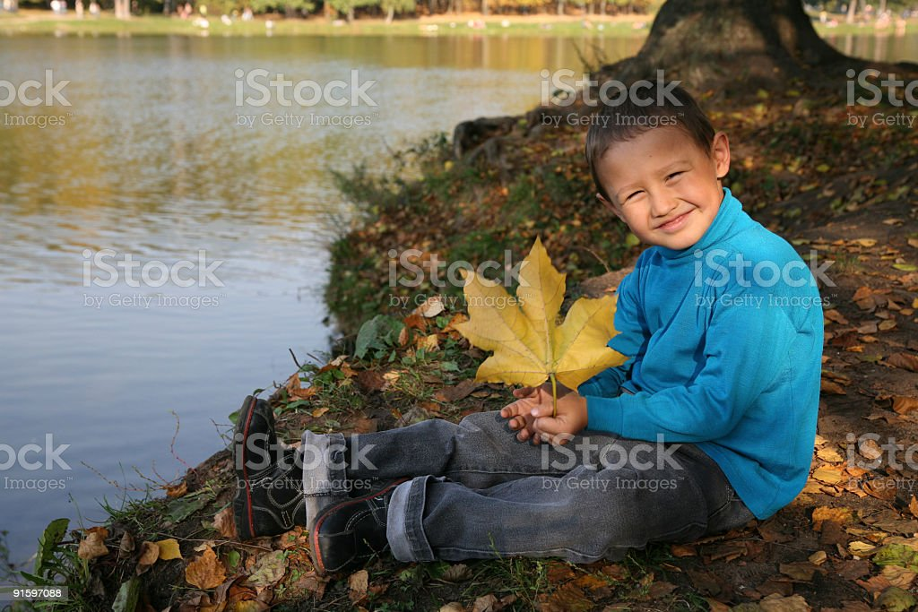 little boy posing with yellow leaf royalty-free stock photo