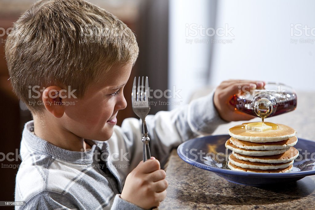 Little boy pouring syrup on pancakes stock photo