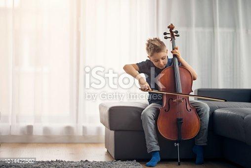Little boy aged 7 practicing cello at home. Nikon D800
