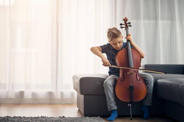 petit garçon pratiquant le violoncelle à la maison - instrument de musique photos et images de collection