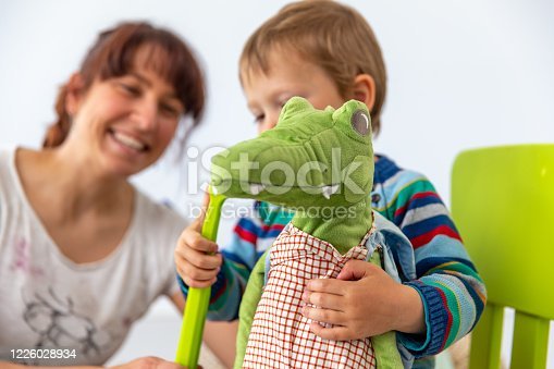 Little Boy Practicing Correct Teeth Brushing on Crocodile Stuffed Toy with his Supportive Mother