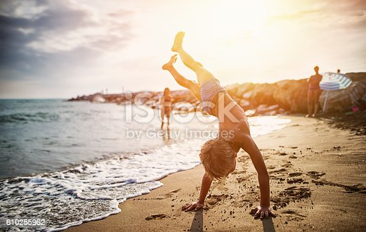 istock Little boy practicing handstand on beach 610255962
