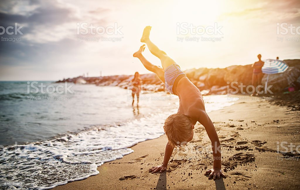 Little boy practicing handstand on beach stock photo