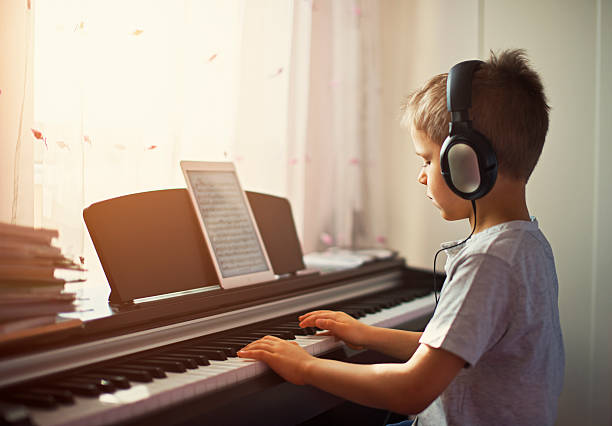 Little boy practicing modern digital piano. Little boy practicing playing digital piano near window on a sunny day.  The boy is using headphones and tablet is displaying the musical notes. pianist stock pictures, royalty-free photos & images