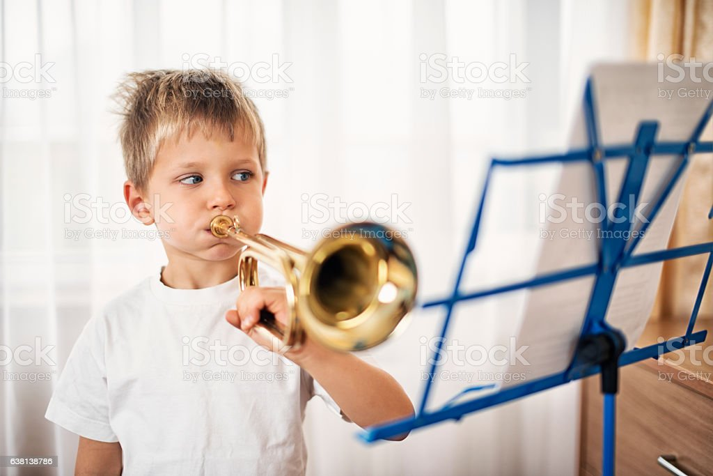 Little boy practicing playing trumpet stock photo