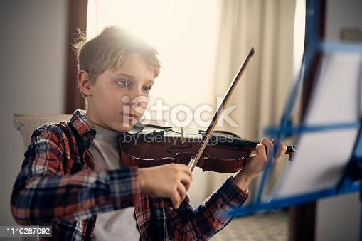 Little boy aged 9 playing violin. A note stand is in front of him. Nikon D850