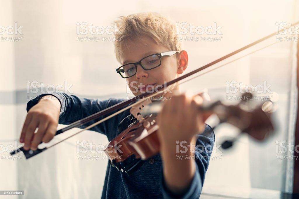 Little boy practicing violin stock photo