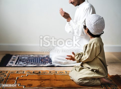 istock Little boy praying alongside his father during Ramadan 958638434