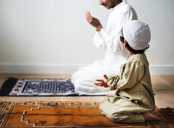 Little boy praying alongside his father during Ramadan stock photo