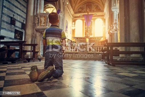 Little boy praying at little church in little Italian town during the Holy Week Nikon D850
