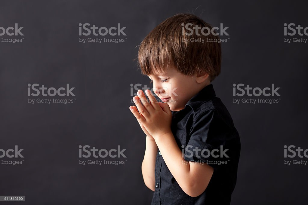Little boy praying, child praying, isolated background stock photo