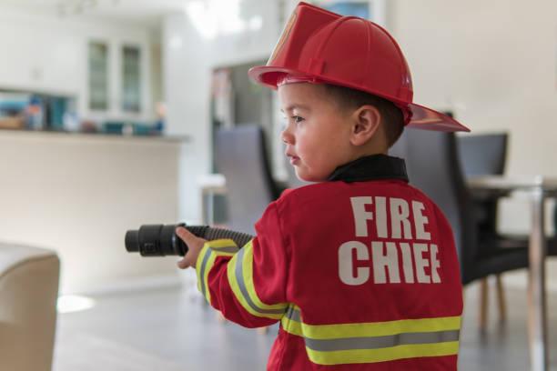 kleiner junge vorgibt, ein feuerwehrmann zu sein - kleine jungen kostüme stock-fotos und bilder