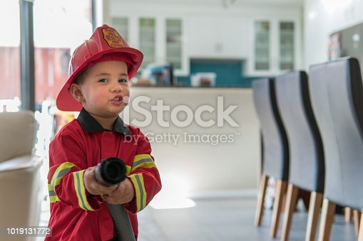 A 3-year old eurasian boy is dressed up in a fireman costume and using a vacuum cleaner hose to pretend that he is putting out a fire