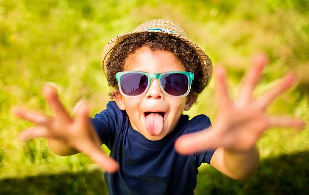 kleine junge ziehen ein gesicht mit waffen outstreched - sonnenbrille kleinkind stock-fotos und bilder