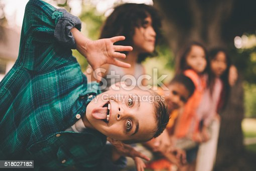 Vintage style shot of a cute little boy leaning over and pulling a silly face for the camera with friends standing on a fence smiling in the background in a summer park