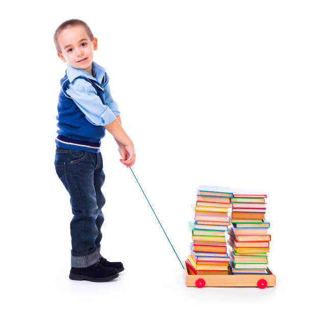 Little boy pulling books in toy cart stock photo