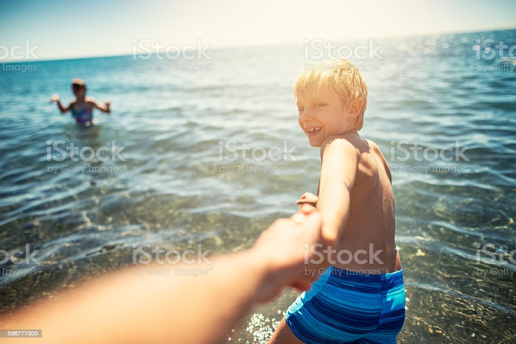 Little boy pulling his father into the sea stock photo