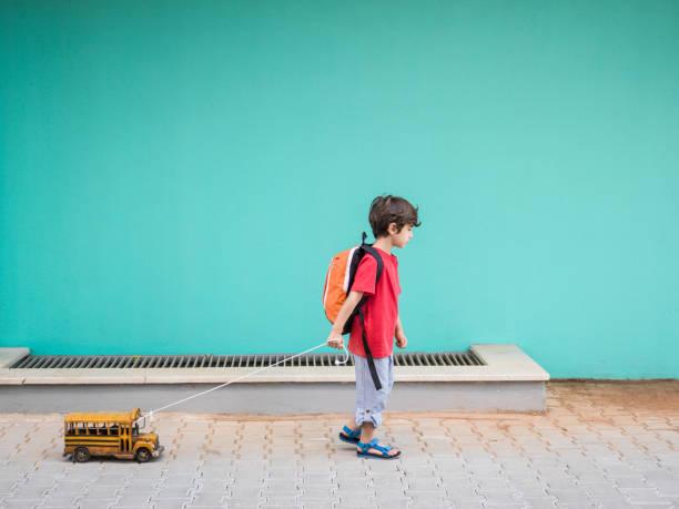 Little Boy Pulling Toy School Bus In Outdoor stock photo