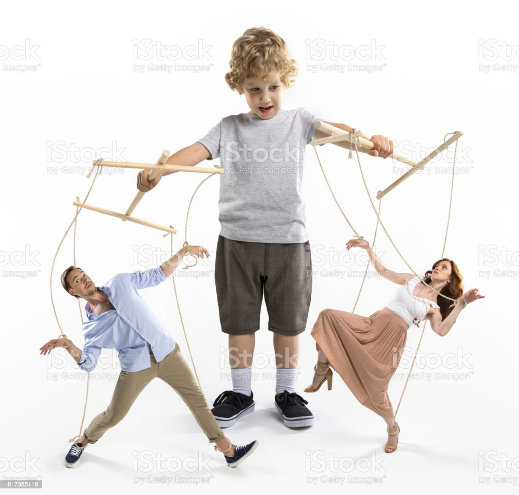 little boy puppeteer controlling parents with strings isolated on white stock photo