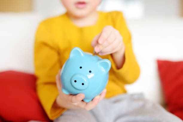 Little boy putting coin into piggy bank Little boy putting coin into piggy bank. Education of children in financial literacy. allowance stock pictures, royalty-free photos & images