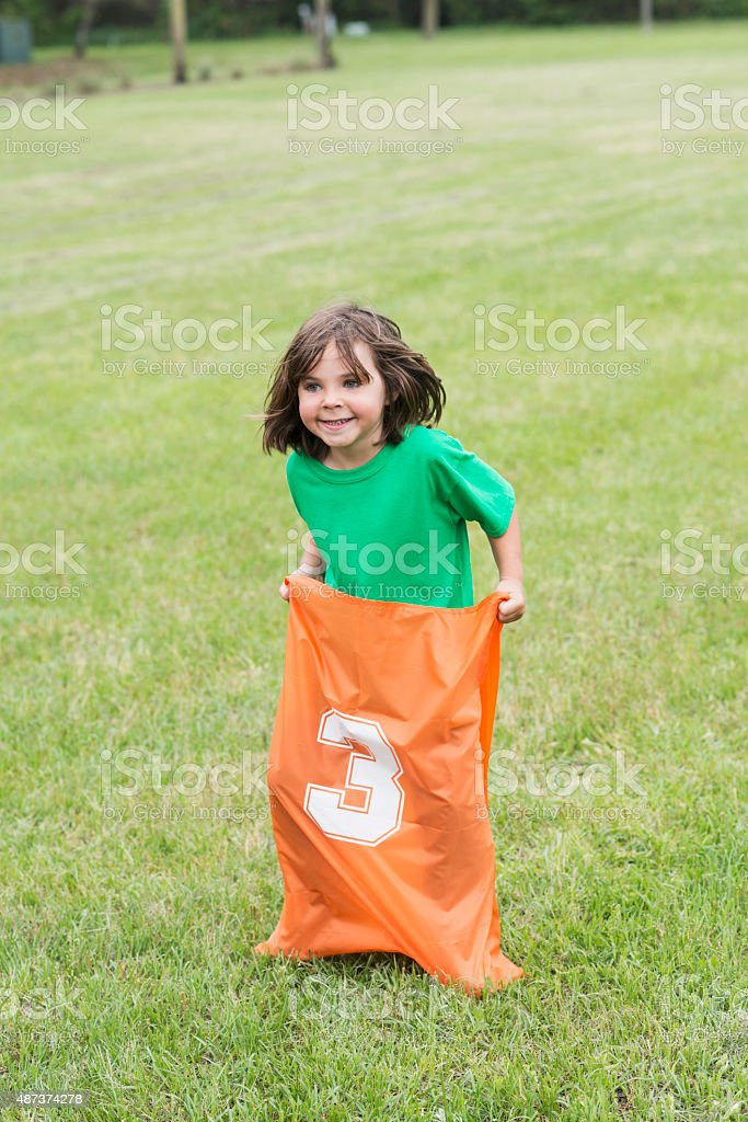 Little boy racing in a sack race stock photo