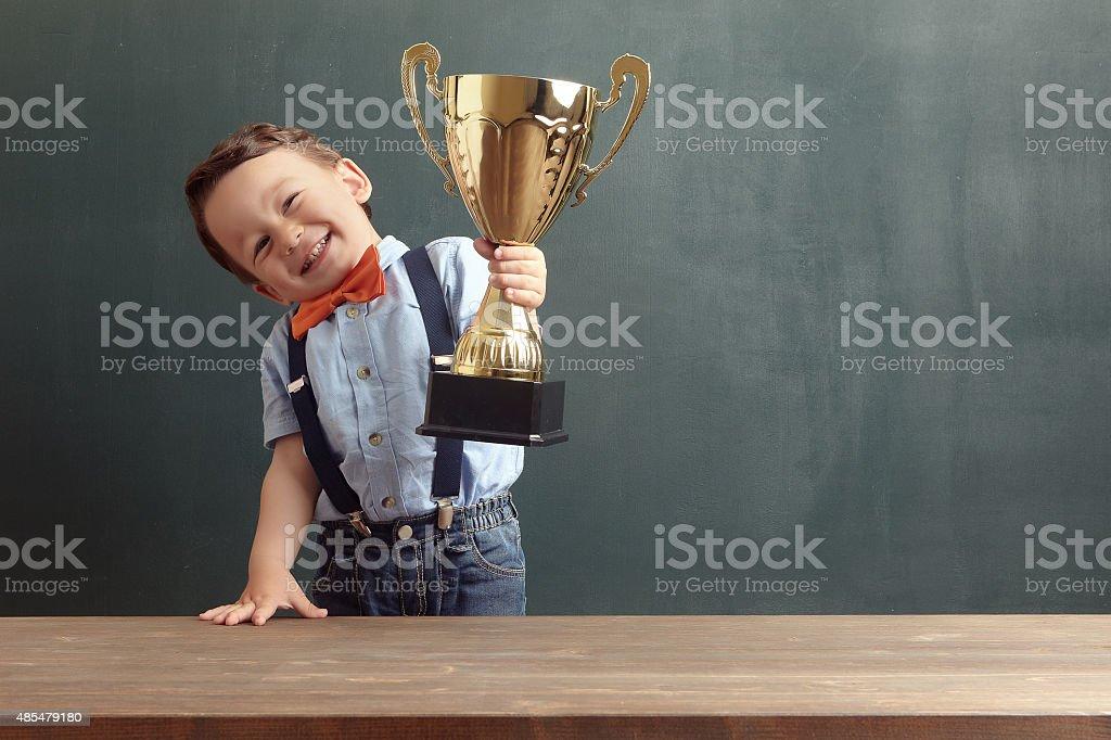 Little boy raising a golden trophy stock photo