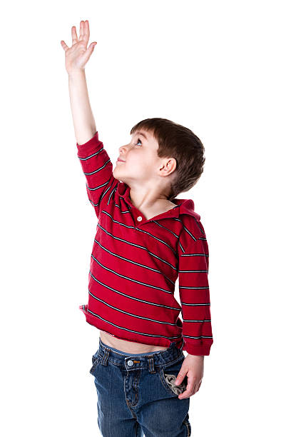 A little boy reaching arm up high against white background stock photo