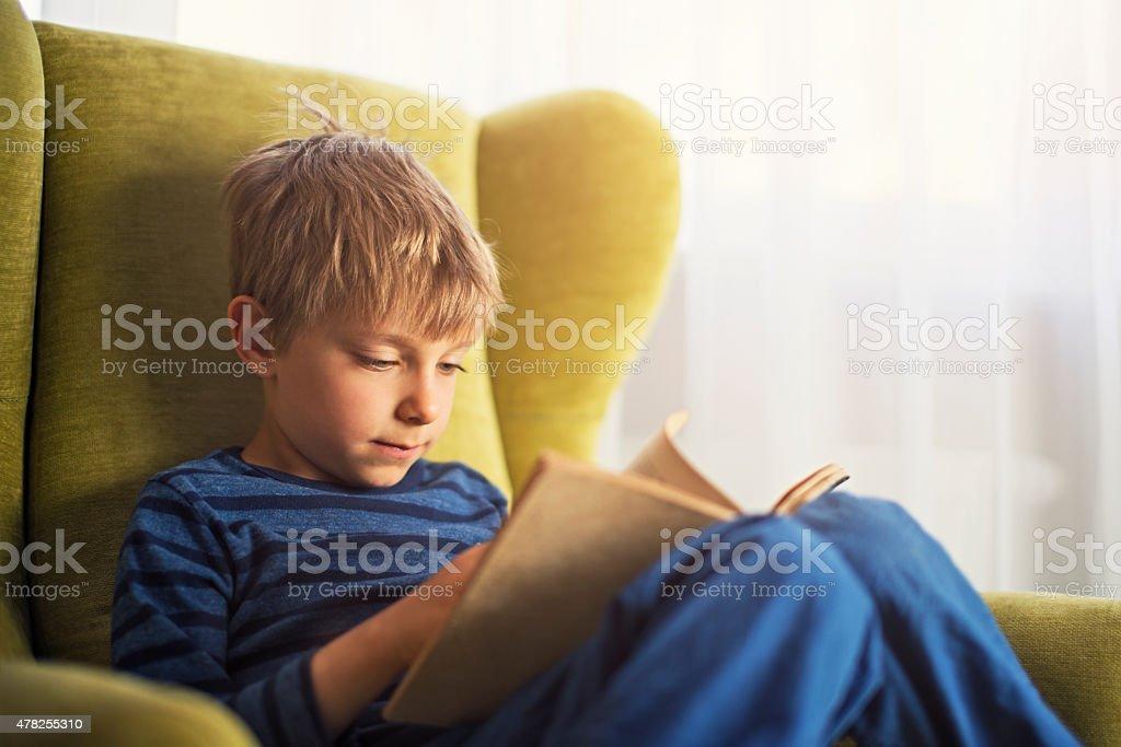 Kleiner Junge liest ein Buch in grünen Sessel – Foto