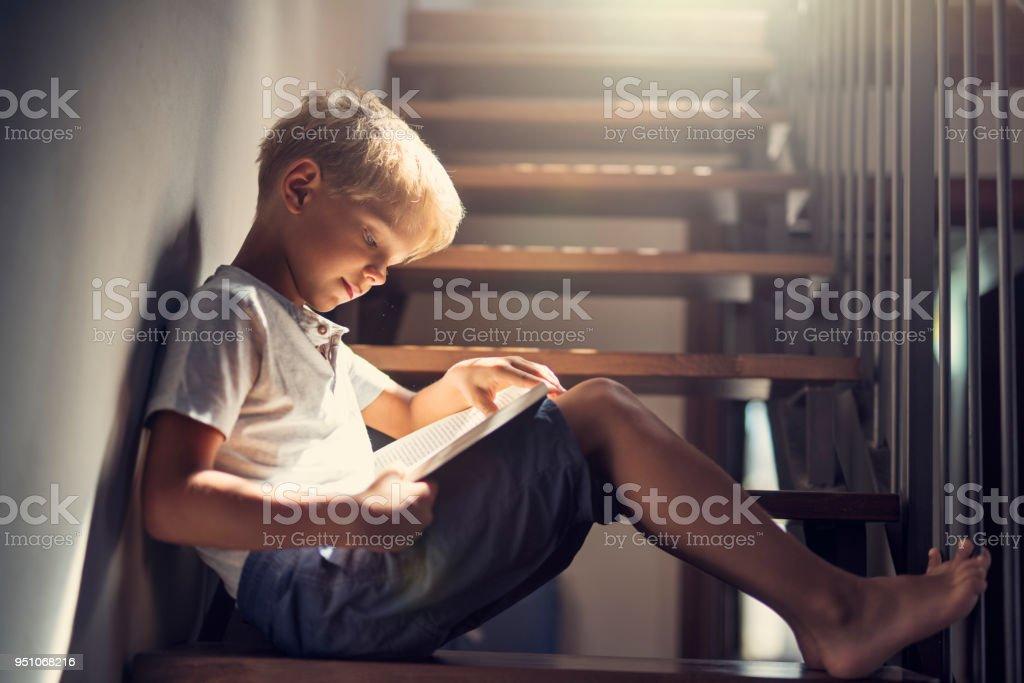 Kleiner Junge, ein Buch auf der Treppe – Foto