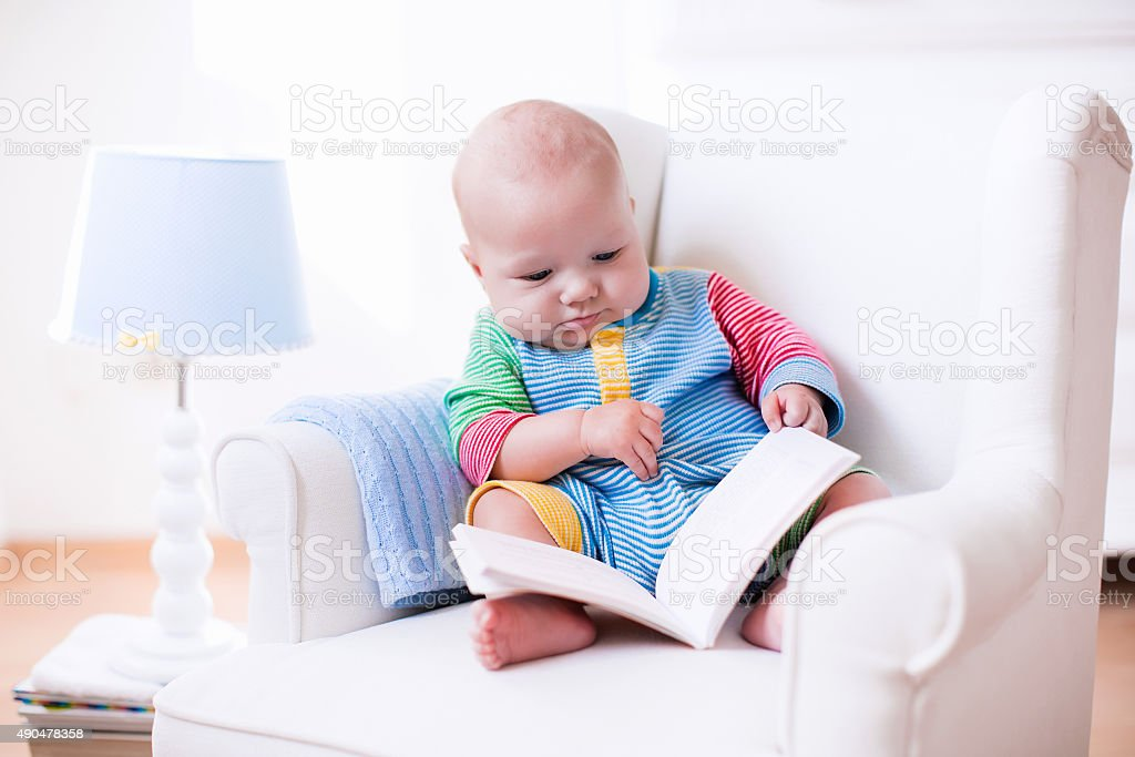 Little boy reading a book stock photo