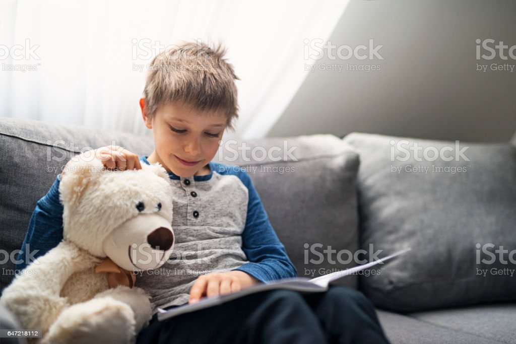 Little boy reading a book to his teddy bear stock photo