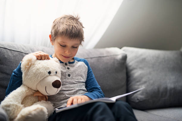 Little boy reading a book to his teddy bear stock photo